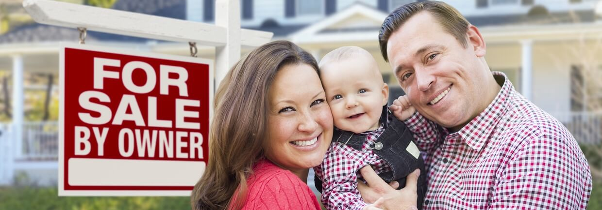 Family In front of a home with a for sale by owner sign